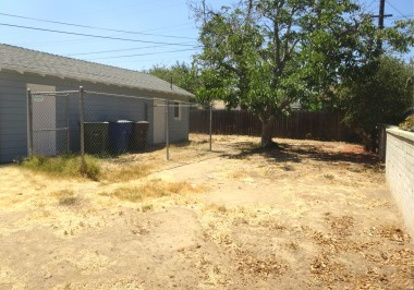 Spacious pool-size backyard with shade  tree, dog run and partial block wall. No  irrigation, but this just means you have a  blank slate to make this yard your own!