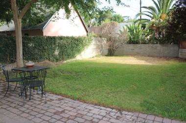 Quaint backyard with shade tree and  block wall.