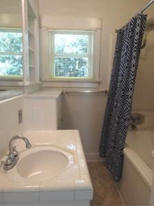 Bathroom with newer linoleum flooring,  large shower head, cabinetry, and  bathtub.