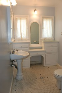 Partially updated bathroom with newer  pedestal sink and toilet, yet still retains  the awesome original tile floor.