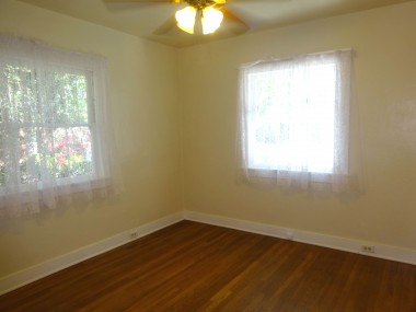 Front bright bedroom with hardwood  floors and ceiling fan.