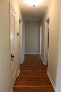 Long gorgeous hardwood floor hallway  to the bathroom and bedrooms.