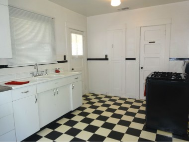 Alternate view of kitchen with original  ironing board and pantry, as well as a  newer free-standing gas range.