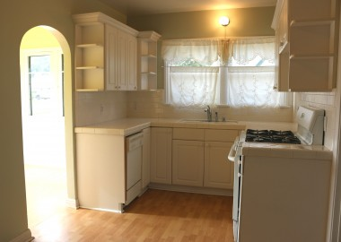 Updated kitchen with dishwasher, gas  range, tile counter tops and breakfast  nook to the left through arched doorway.