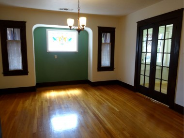 Gorgeous original hardwood floors and original wood trim in spacious living room. Wood-burning fireplace with insert that actually heats the room (charming tea kettle  humidifier included).