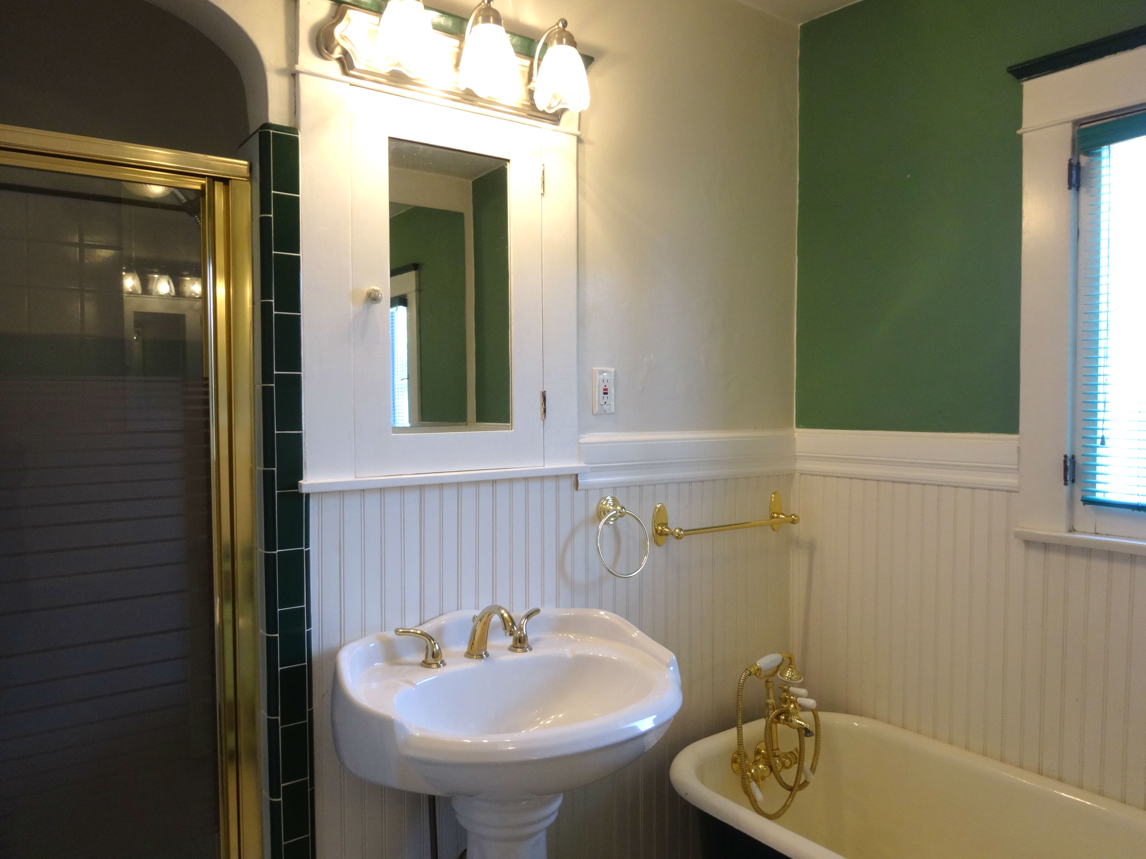 Bathroom with tile floor, wainscoting, newer pedestal sink and commode, with separate shower and a vintage claw foot tub!