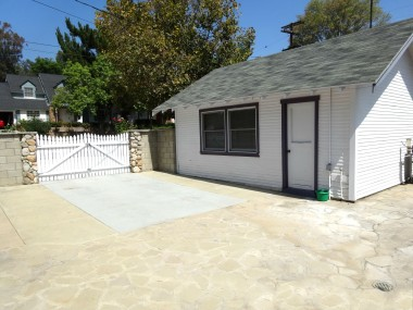 Huge driveway/backyard area with detached garage. Spacious enough to enlarge the garage, or use this area for gated parking. Or set up tables and chairs for a barbecue and watch the 4th of July fireworks! This backyard also has installed drains.  These homeowners have thought of everything!