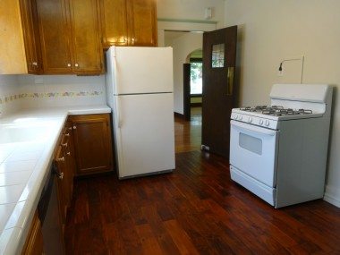 Alternate view of kitchen with tile counter tops, and original wood swinging door that leads to the formal dining room.  Current homeowners have entertained as many as 22 people very comfortably in this home!