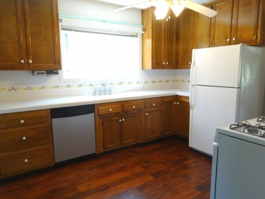 Lovely updated kitchen with newer engineered wood flooring, dishwasher, gas stove, refrigerator, greenhouse window and ceiling fan.