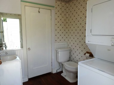 Indoor laundry room with stackable washer/dryer, doubles as a half bath with newer commode and sink.