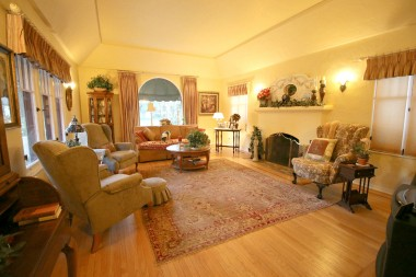 Gorgeous living room with original hardwood floors and original sconce lighting.