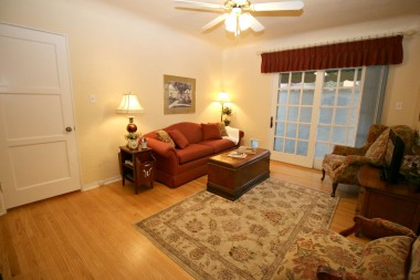 One of the three bedrooms, currently used as a TV room. Note the newer sliding French doors and original hardwood floors.