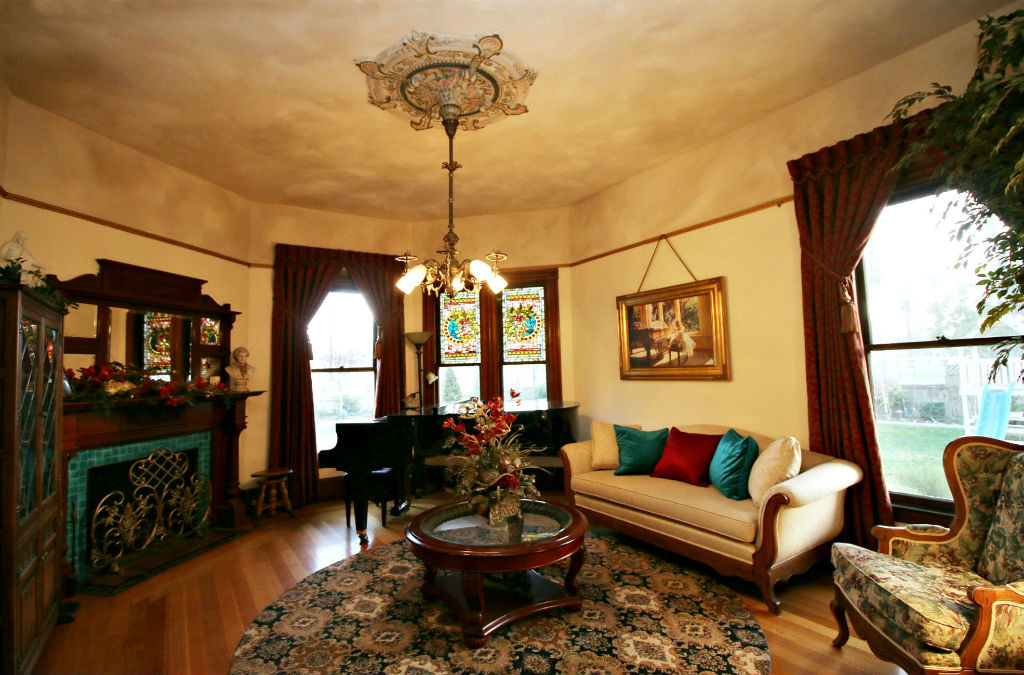 Formal living room with original light fixture and medallion, as well as gas fireplace #2 and original stained glass in windows above grand piano. Another example of the early Riverside residents' wealth were push button light and dimmer switches, which still operate today!