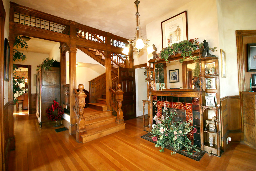 Alternate view of foyer as you enter the home. One of SIX working gas fireplaces with original tile surround and wood mantle. Doorway to the left of fireplace leads to downstairs bathroom.