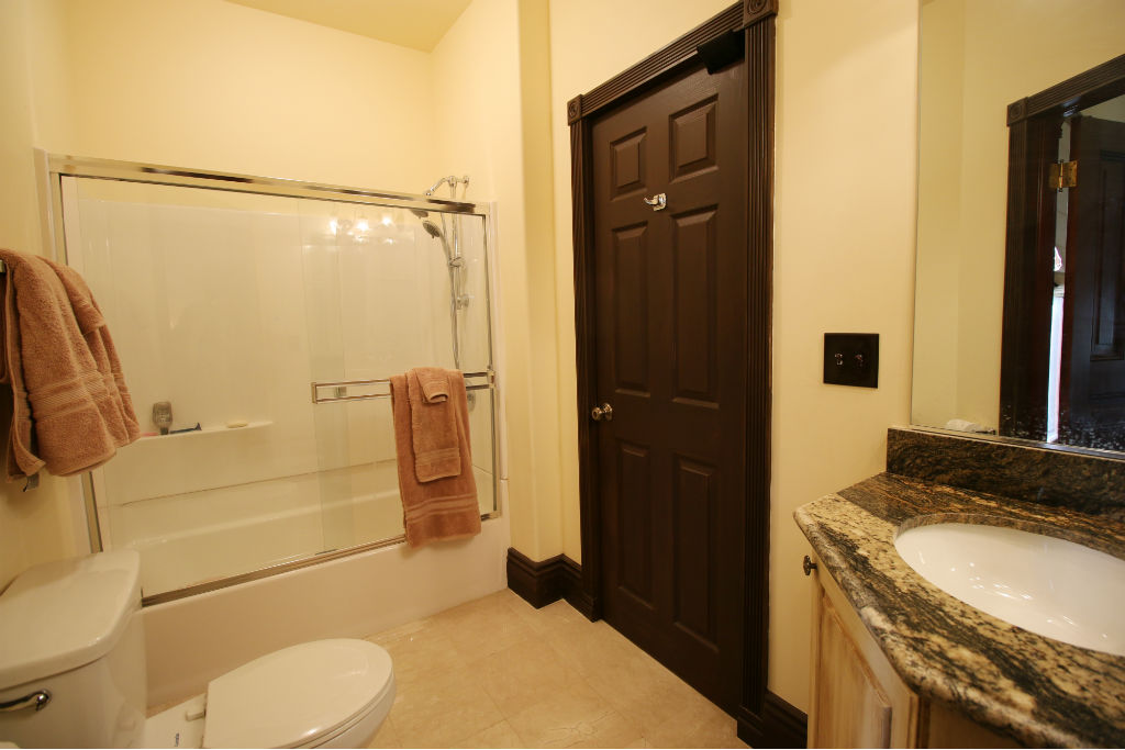 Jack and jill bathroom that is shared by 3rd and 4th bedrooms. Shower in tub, granite counter top, tile floor.