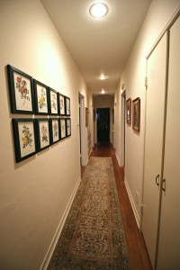 Long hallway with hardwood floors, original telephone alcove, and the 10-picture wall arrangement will stay if buyer wishes to keep.