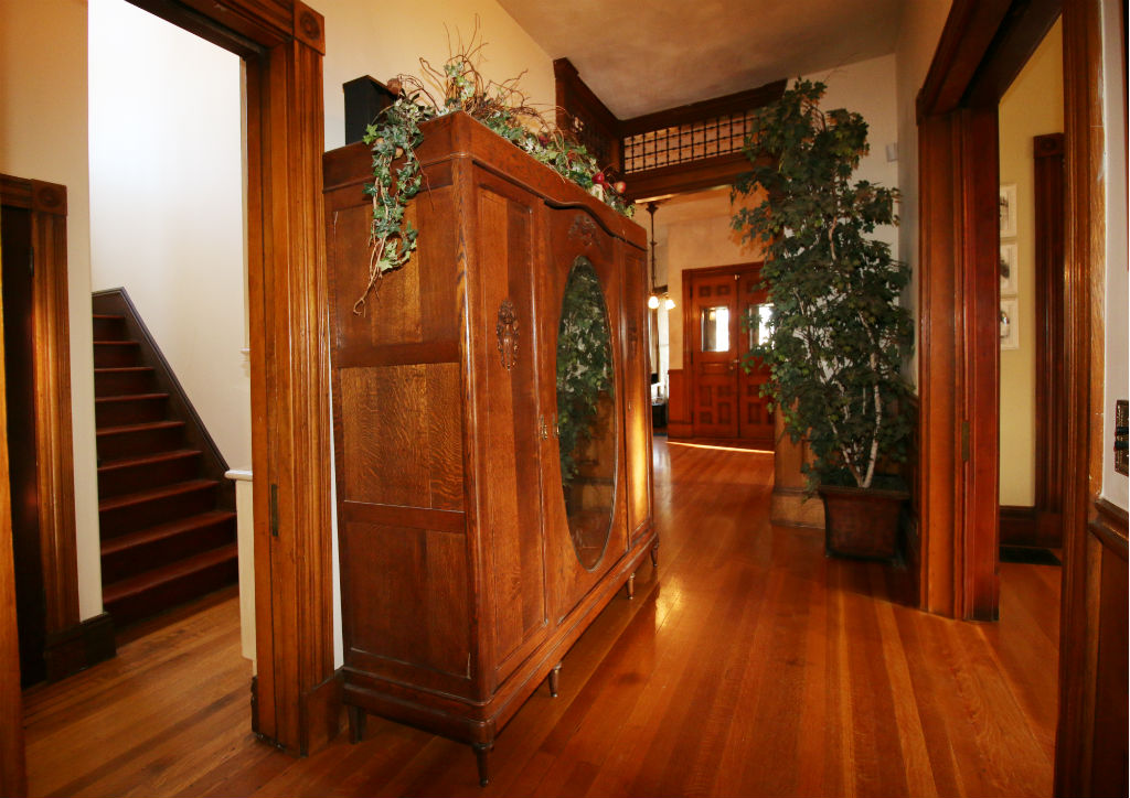 Servants' staircase to the left (next to the kitchen), and this hallway leads you full circle and back to the front entrance, the office enclave, and the downstairs bathroom. To the right are the pocket doors leading to formal dining room.