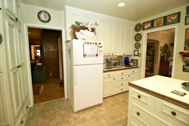 Loads of kitchen cabinetry, recessed lighting, newer flooring, and refrigerator stays.