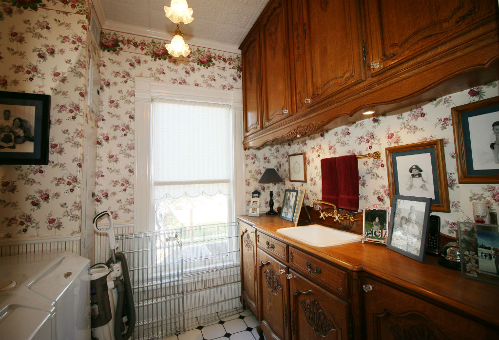 Convenient upstairs laundry room with tile floor, real tin (period accurate) ceiling, with sink and antique cupboards.