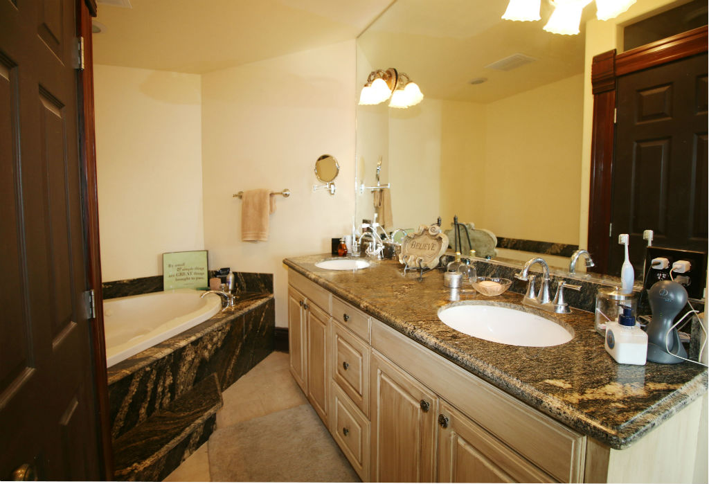 Master bathroom boasts dual sinks with granite counter top, spa tub, and private water closet.