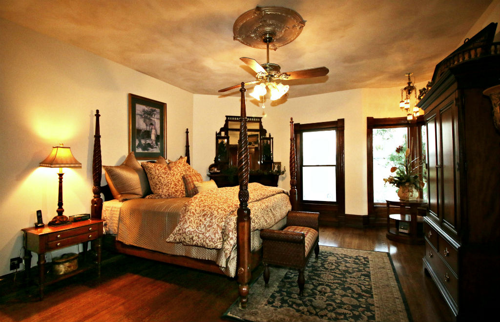 Master bedroom suite with gas fireplace #5, ceiling fan, hardwood floors and original 10-inch base boards.