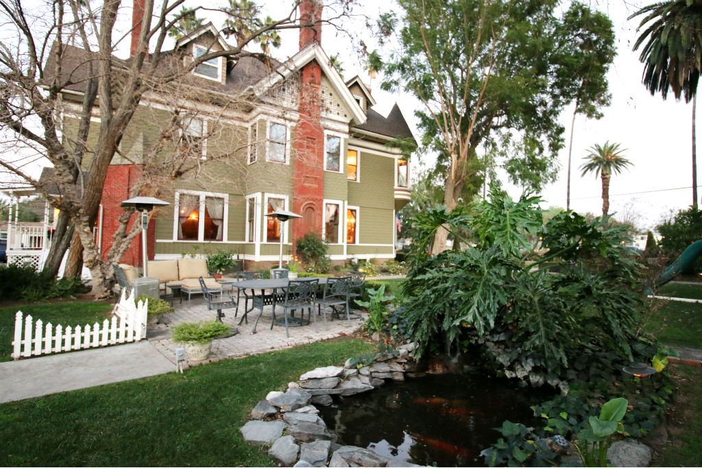 Alternate view of side yard with koi pond in foreground (extensive pump and waterfall system), patio area, and driveway with lots of parking (and room for a 4-car garage) to the left.