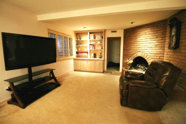 Family room off the kitchen with gas fireplace, plantation shutters and recessed lighting.