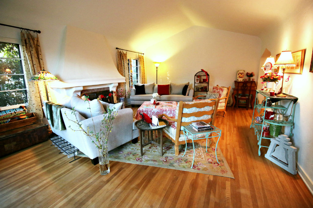 Large living room with gorgeous original hardwood floors, dramatically high ceiling, and wood-burning fireplace.