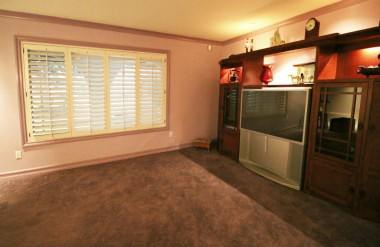 Alternate view of living room with plantation window shutters overlooking the front porch.