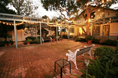 Backyard at dusk with twinkle lights in full effect. Relax in your low-maintenance backyard and enjoy the scent of the orange blossoms and rose bushes while enjoying the elegance of living in the quiet Wood Streets neighborhood.
