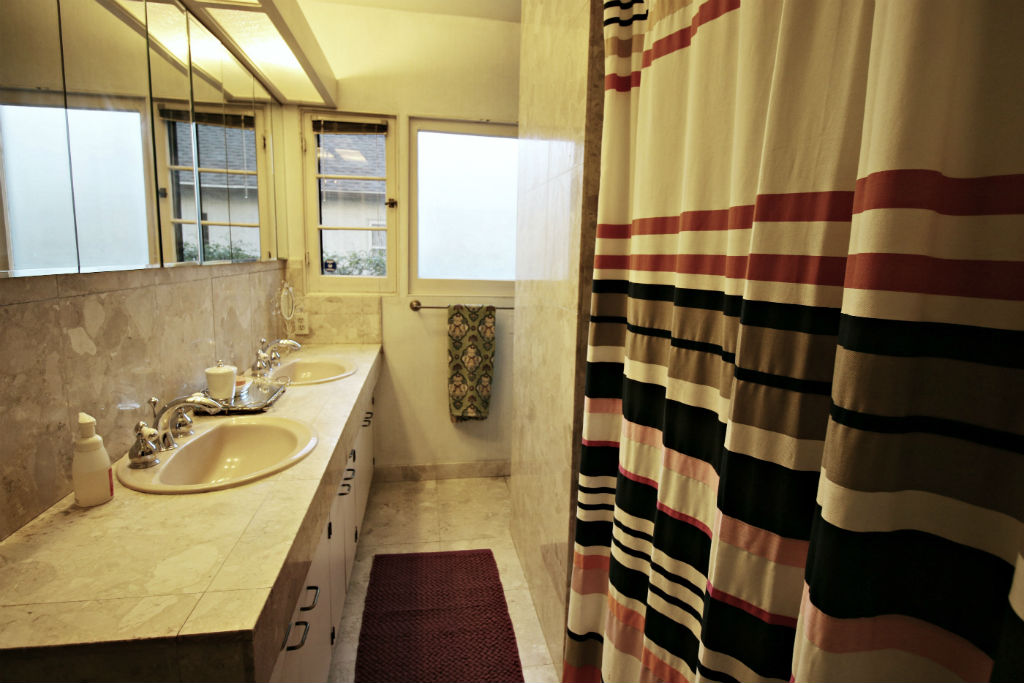 Hall bathroom has been updated with dual sinks and tiled shower enclosure with tub.