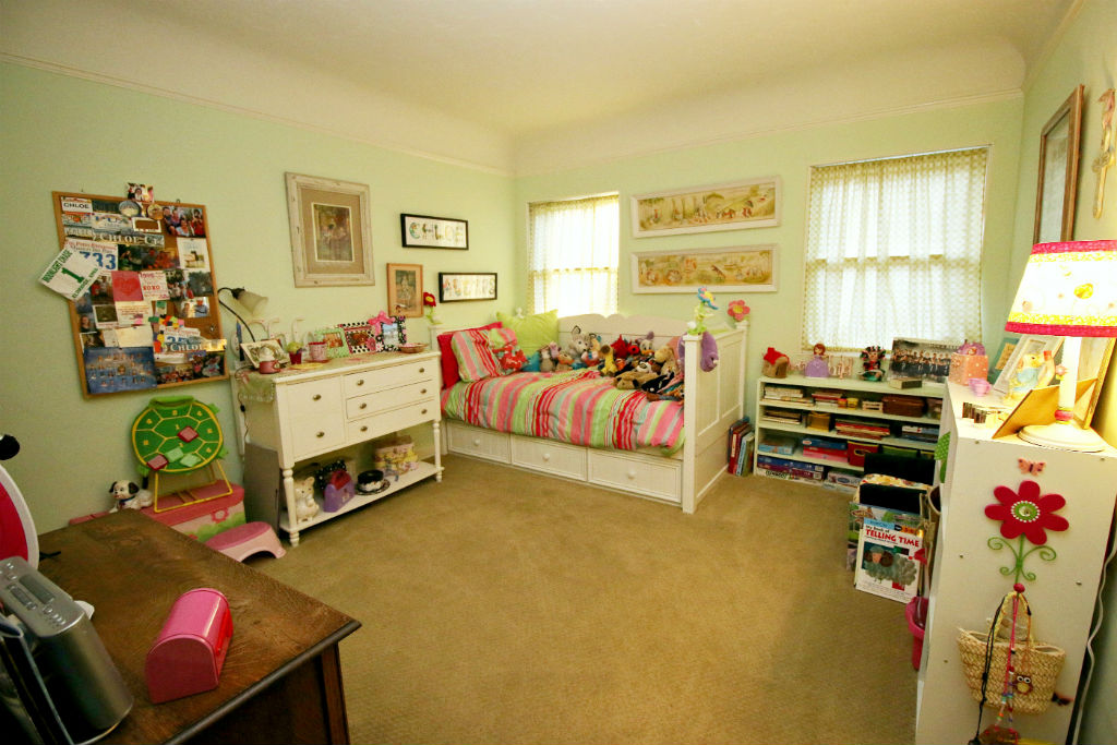 Downstairs bedroom with walk-in closet and carpeting over hardwood floors. Coved ceiling.