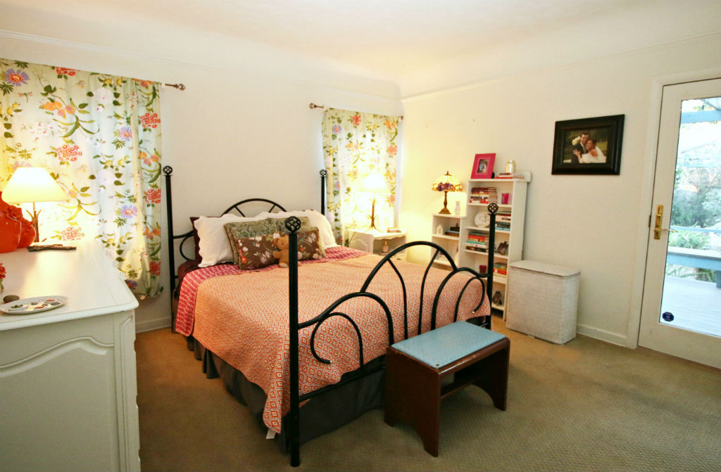 Large downstairs bedroom with walk-in closet and door to back patio.
