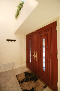 Double door entry with tile flooring and plant shelf above doorway with unique round window to allow in natural light.