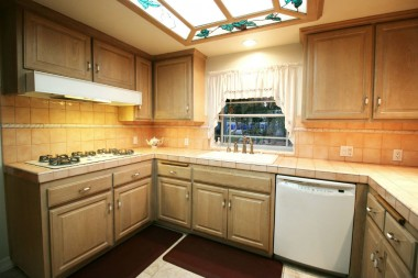 Upgraded kitchen with tile floor, tile counters, dishwasher, garden window, and newer 5-burner range, microwave and oven.