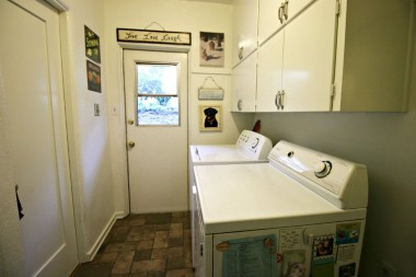 Separate laundry room downstairs with lots of cabinetry.