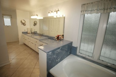 Private master bathroom with large closet, dual sinks, soaking tub, and separate shower.