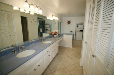 Alternate view of master bathroom with large closet space and dual sinks, and tile flooring.