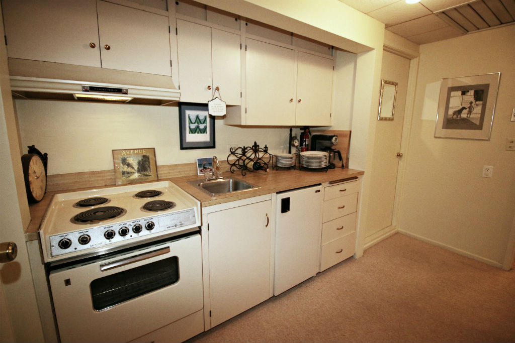 Upstairs kitchenette with refrigerator, sink, and stove. Door to the right is access to huge attic space.