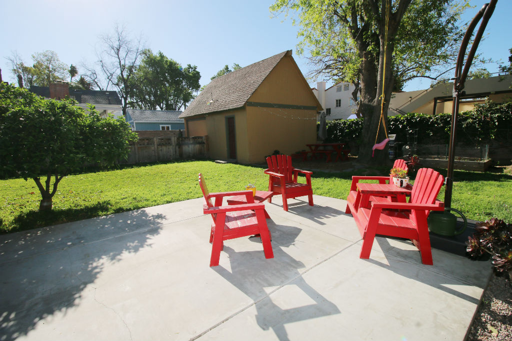 Detached garage, grassy area, patio area, mature tree with swing, garden area, citrus tree, newer fence along the driveway. Cute, cute, cute!