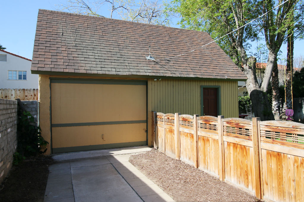 Garage was rebuilt with permits about 40 years ago. Two-car in size, but one-car size door, but tons of storage inside, including a stairway to an attic with even more storage!