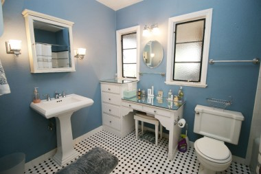 Updated hallway bathroom with tile floor, pedestal sink and built-in makeup desk. Shower in tub.