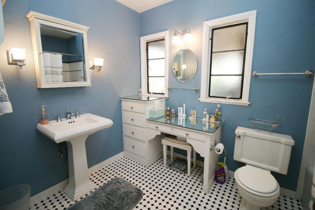 Elegant Updated hallway bathroom with tile floor pedestal sink and built in makeup desk