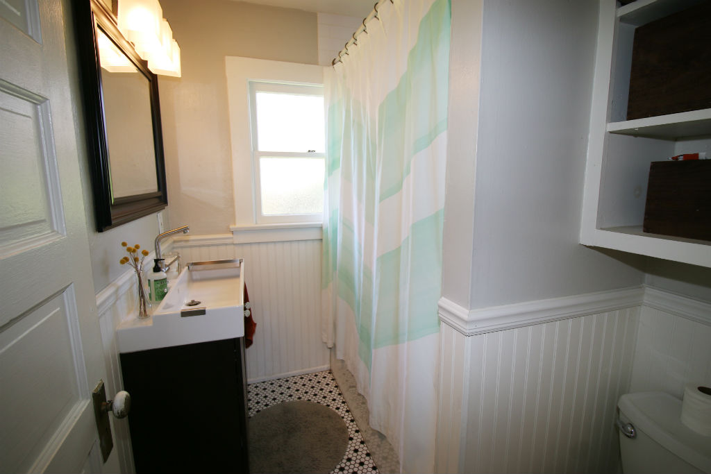 Remodeled hallway bathroom with tile floor, newer sink, shower in tub, and charming bead board.