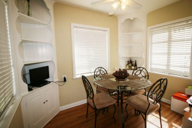 Bright and cheery breakfast nook with two built-in corner hutches.