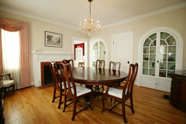 Formal dining room with built-in display curios, original hardwood floors, and fireplace.