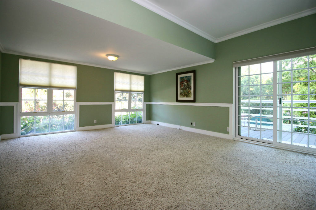 Large family room overlooking the park-like backyard with built-in pool, deck and patio areas.