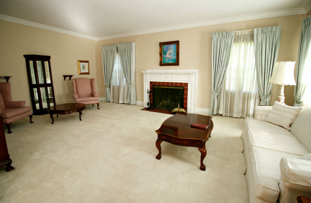 Formal living room with fireplace and original handcrafted mantle.
