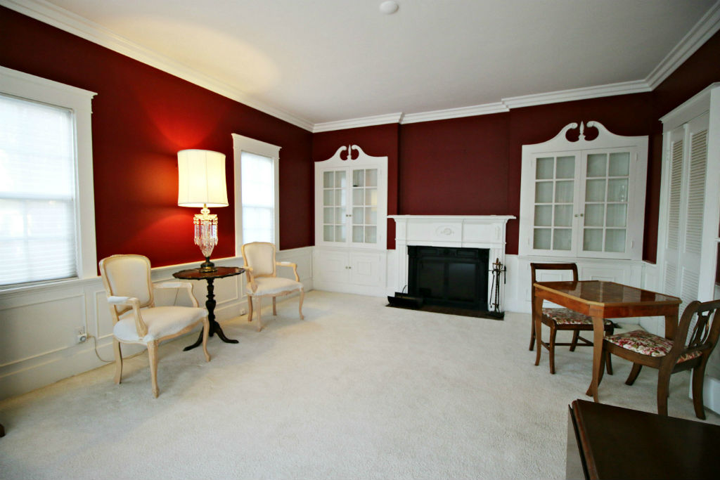 Front parlor with fireplace and additional built-in shelving units.