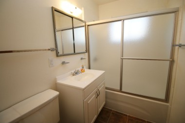 Hallway bathroom with shower in tub and sliding glass privacy doors.